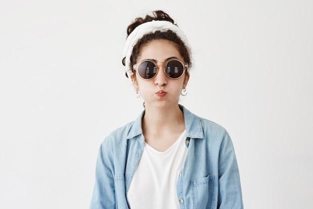 Engraçado modelo feminino com cabelos escuros nos lábios faz beicinho, camisa jeans e óculos de sol redondos, faz uma careta como está. alegre mulher bonita se diverte dentro de casa, sopra bochechas
