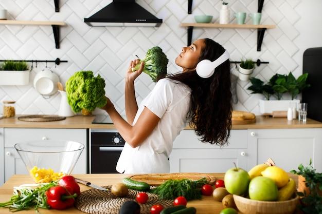 Engraçado mulata em grandes fones de ouvido sem fio está dançando com salada de folhas e brócolis na cozinha moderna perto da mesa cheia de legumes e frutas