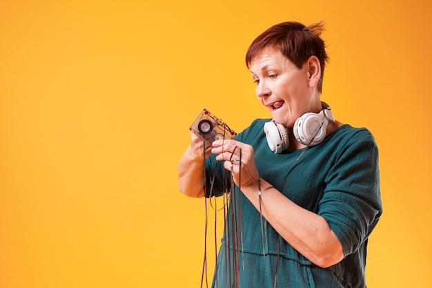 Engraçado mulher sênior brincando com fita cassete