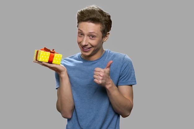 Engraçado rapaz adolescente segurando a caixa de presente. adolescente alegre bonito aparecendo o polegar enquanto segura a caixa de presente. isolado em fundo cinza.