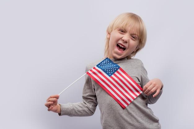 Engraçado rapaz loiro segurando uma bandeira americana em fundo branco. viajar para os eua com crianças.