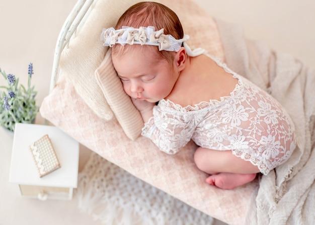 Engraçado recém-nascido dormindo na cama pequena