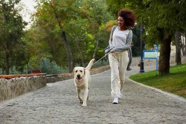 Engraçado senhora saudável correndo de manhã com seu cachorro no parque