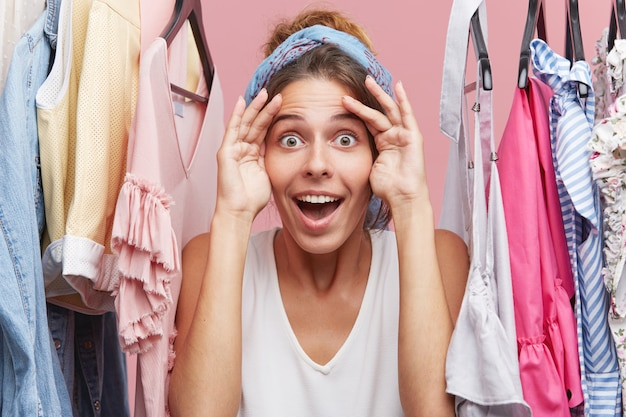 Engraçado vendedor feminino de roupas, olhando para a distância, à espera de compradores em pé perto de prateleira com roupas. mulher feliz, mantendo as mãos na testa, olhando para a distância, esperando por alguém