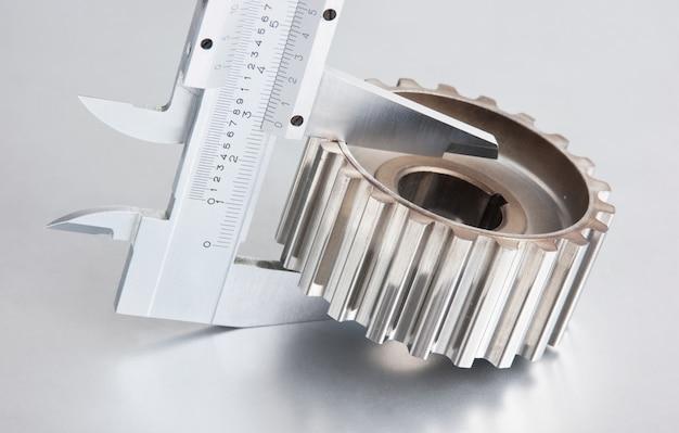Engrenagem e pinças em uma placa de metal
