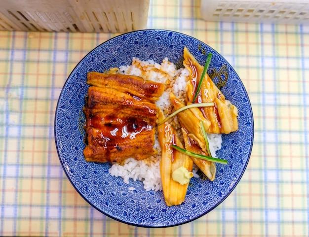 Enguia kabayaki grelhada com atum cru no arroz em tigela azul na vista superior