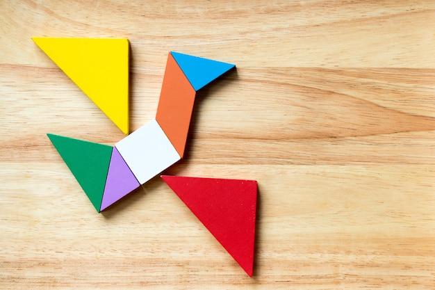 Enigma do tangram da cor na forma do pássaro de voo no fundo de madeira