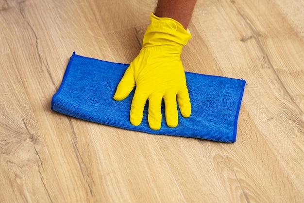 Enluvada para lavar um piso laminado à mão com um pano úmido