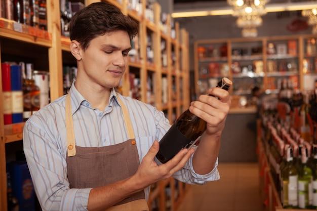 Enólogo masculino jovem bonito vestindo avental, segurando a garrafa de vinho, copie o espaço