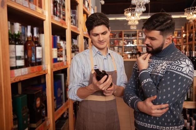 Enólogo profissional, ajudando seu cliente masculino a escolher o vinho tinto. homem barbudo falando com sommelier no supermercado