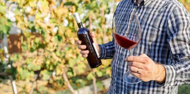 Enólogo segurando copo e garrafa de vinho