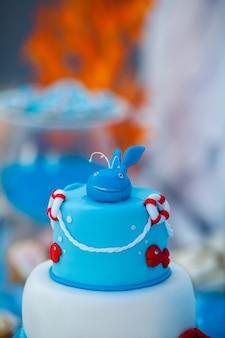 Enorme bolo de aniversário azul e branco com doce caranguejo, peixe, estrelas do mar e baleia engraçada no topo