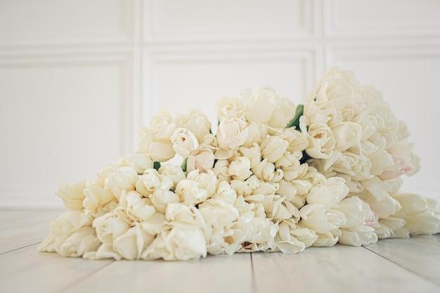 Enorme buquê de tulipas brancas sobre fundo branco de páscoa em piso de madeira