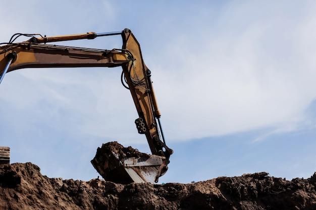 Enorme escavadeira escavadeira com pá pesada em canteiro de obras de cascalho no céu