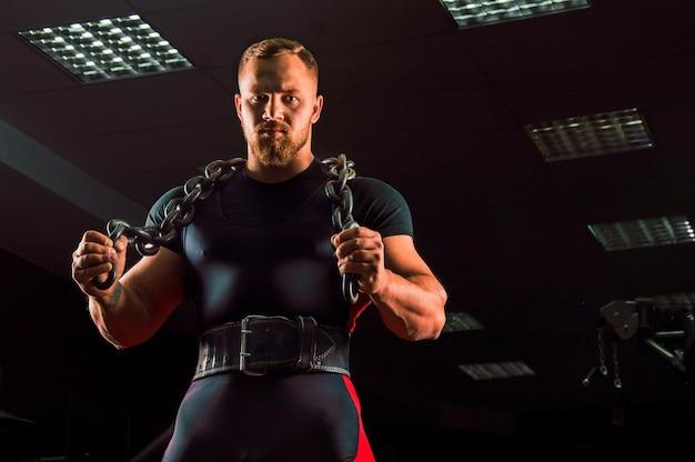 Enorme levantador de peso com uma corrente em volta do pescoço está na academia