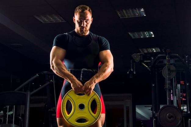 Enorme levantador de peso em pé com um peso nas mãos na academia