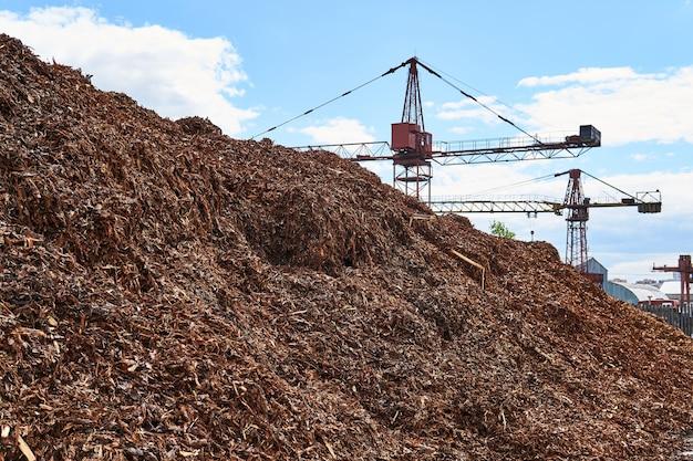 Enorme pilha de casca de madeira picada removida de toras em uma fábrica de madeira e guindastes