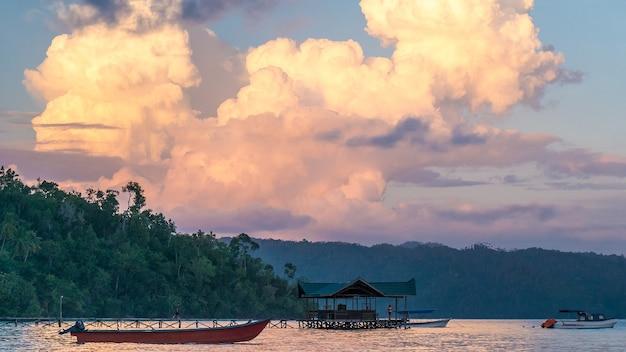 Enormes nuvens brancas acima da estação de mergulho em sunset, homestay gam island, west papuan, raja ampat, indonésia