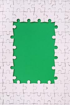 Enquadramento na forma de um retângulo, feito de um quebra-cabeça branco em torno do espaço verde