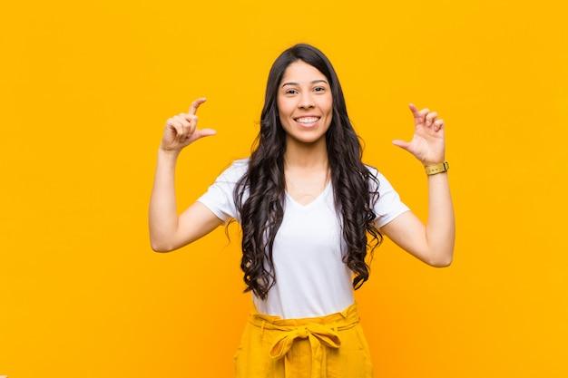 Enquadrar ou delinear o próprio sorriso com as duas mãos, olhando positivo e feliz, conceito de bem-estar