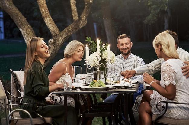 Enquanto as taças de vinho estão vazias, vamos experimentar aquela comida vegetal. grupo de amigos adultos tem um descanso e uma conversa no quintal do restaurante à noite.