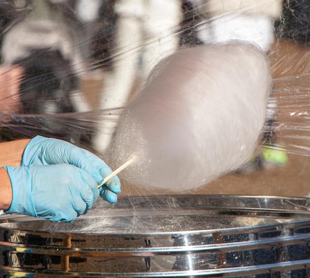 Enrolado à mão algodão doce em máquina de linha de doces