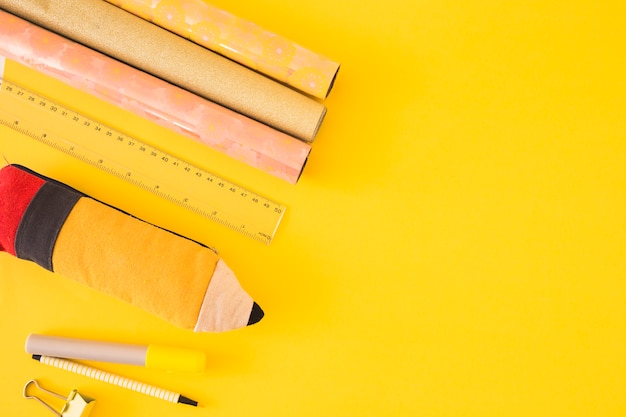 Enrolado em papel de presente, caso e caneta de feltro e pino de bulldog em fundo amarelo
