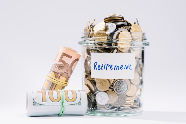 Enrolado notas e contêiner de aposentadoria cheia de moedas no fundo branco