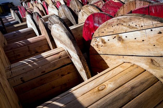 Enroladores de cabo de madeira grandes, armazenados em uma fábrica de cabos elétricos.