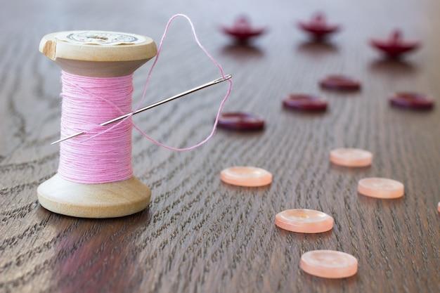 Enrole a linha rosa com uma agulha. botões rosa e clarete