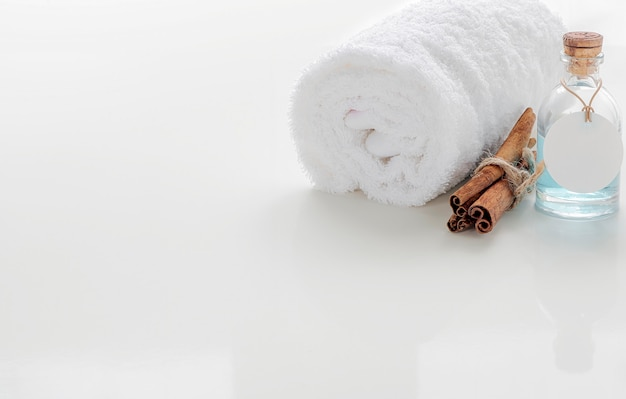 Enrole as toalhas brancas com garrafa de óleo na mesa branca.