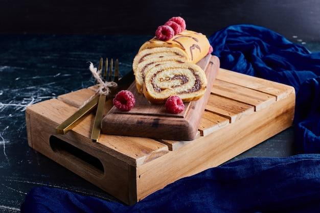 Enrole o bolo com chocolate e frutas em uma bandeja de madeira.