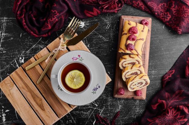 Enrole o bolo com chocolate, frutas vermelhas e uma xícara de chá.