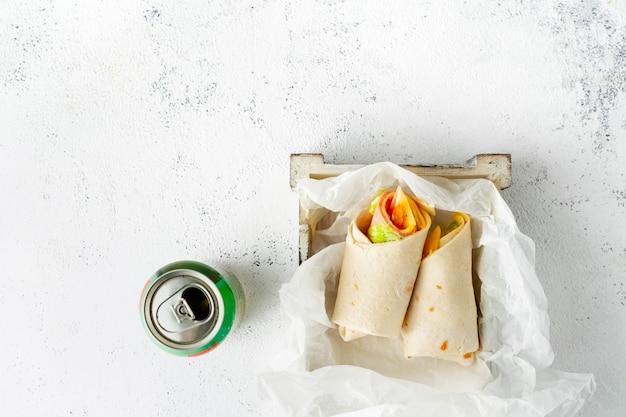 Enrole o sanduíche com presunto, queijo e legumes, lata de refrigerante