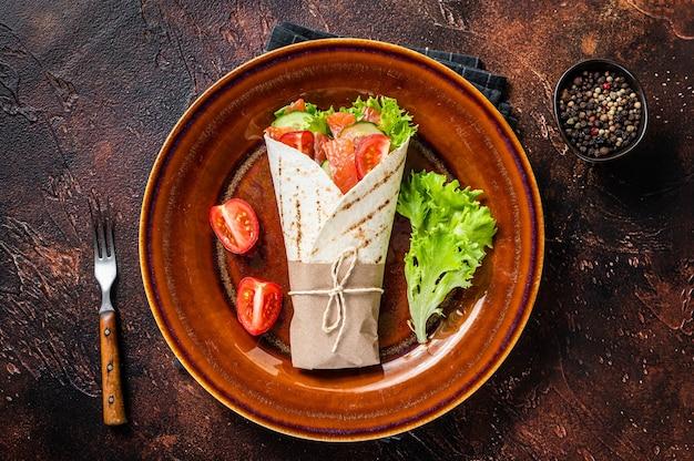 Enrole o sanduíche de rolo com peixe, salmão e vegetais. fundo escuro. vista do topo.