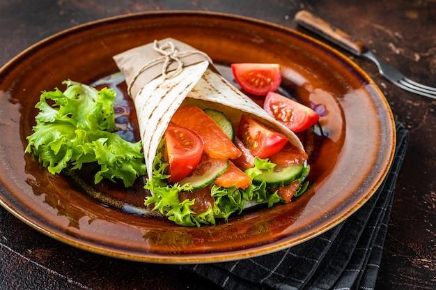 Enrole o sanduíche de rolo com salmão e legumes. fundo escuro. vista do topo.