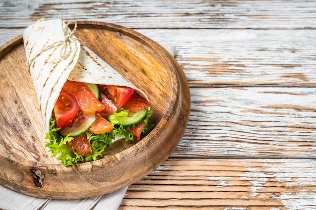 Enrole o sanduíche de salmão, enrole com peixe e vegetais. fundo de madeira branco. vista do topo. copie o espaço.