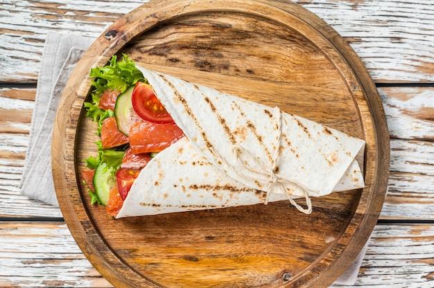 Enrole o sanduíche de salmão, enrole com peixe e vegetais. fundo de madeira branco. vista do topo.