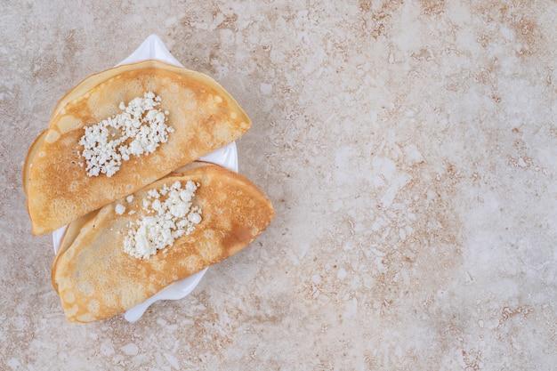 Enrole panquecas com queijo cottage e leite