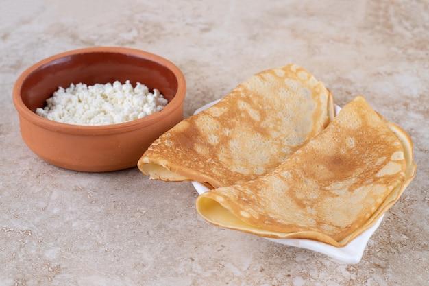 Enrole panquecas com queijo cottage e uma tigela de barro