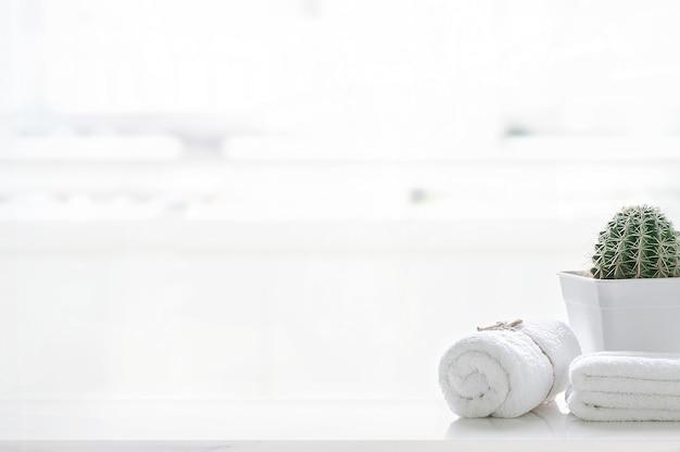 Enrole toalhas brancas na mesa branca com espaço de cópia no fundo desfocado da sala de estar. para montagem da exposição do produto.
