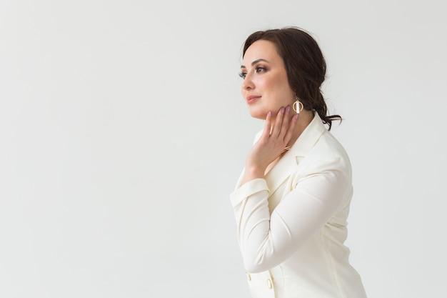 Ensaio de alta moda de jovem morena com penteado elegante em um terno branco dentro de casa. pessoas de negócios e o conceito de estilo moderno. copie o espaço.