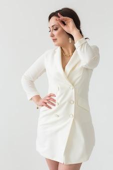 Ensaio de alta moda de jovem morena com penteado elegante em um terno branco dentro de casa. pessoas de negócios e o conceito de estilo moderno.
