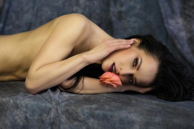 Ensaio de beleza da modelo morena nua sedutora com uma rosa na boca, posando no estúdio