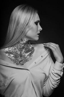 Ensaio de beleza em preto e branco: fabulosa modelo loira posando no estúdio com maquiagem brilhante e papel alumínio no pescoço