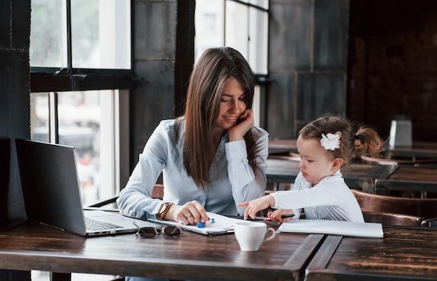Ensinando a filha. mulher de negócios com roupa oficial com criança está dentro de casa no café durante o dia.