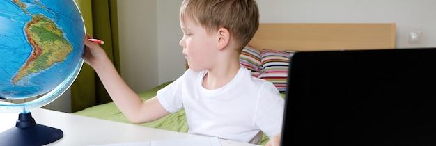 Ensino à distância, aula de geografia. o menino está sentado na cama com um globo no laptop.