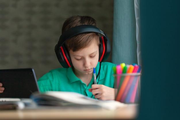Ensino a distância criança escrevendo trabalhos de casa com tablet digital. educação on-line do conceito.