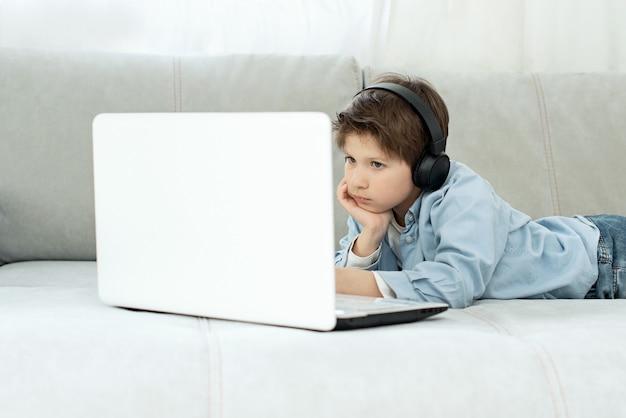 Ensino a distância durante isolamento durante quarentena em coronovírus. menino e laptop em casa. estilo de vida. jogo viciado. jogo on line