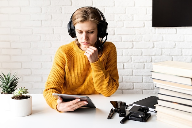Ensino à distância. e-learning. jovem mulher pensativa com suéter amarelo e fones de ouvido pretos, estudando on-line usando o tablet digital